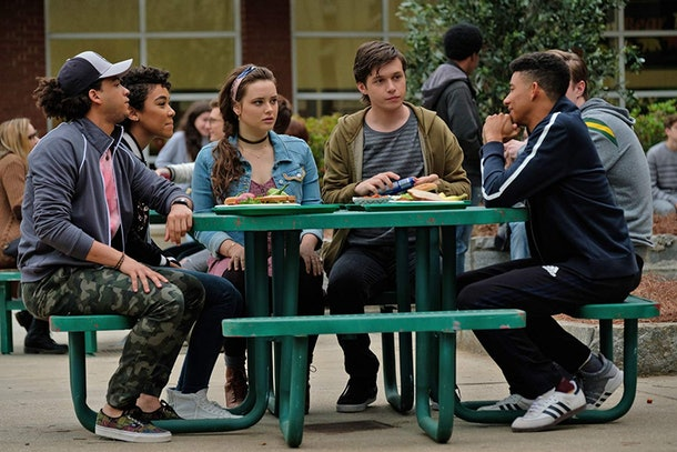 A group of high school friends sits around a table outside their school and talks in 'Love, Simon.'