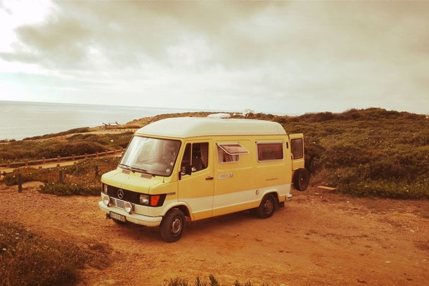 The Aurora Campervan has a yellow exterior and is located in a national park in Portugal.