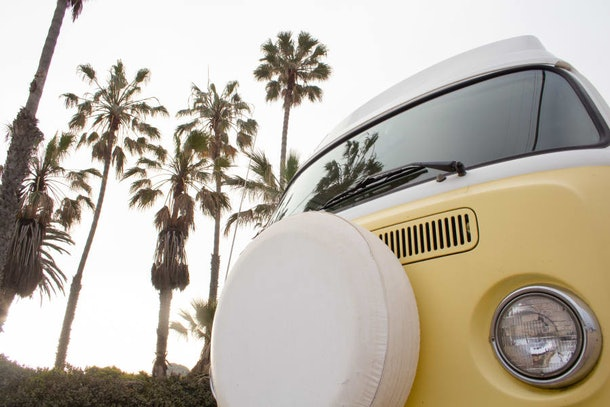 A 1971 Volkswagen Westfalia is yellow and very vintage-looking against a sky filled with palm trees.