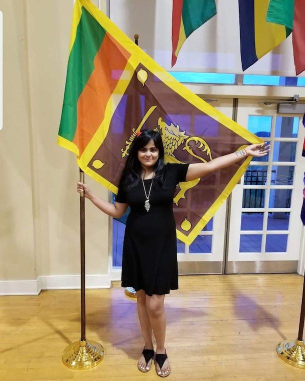 Berea College student Ishara Nanayakkara standing with a flag