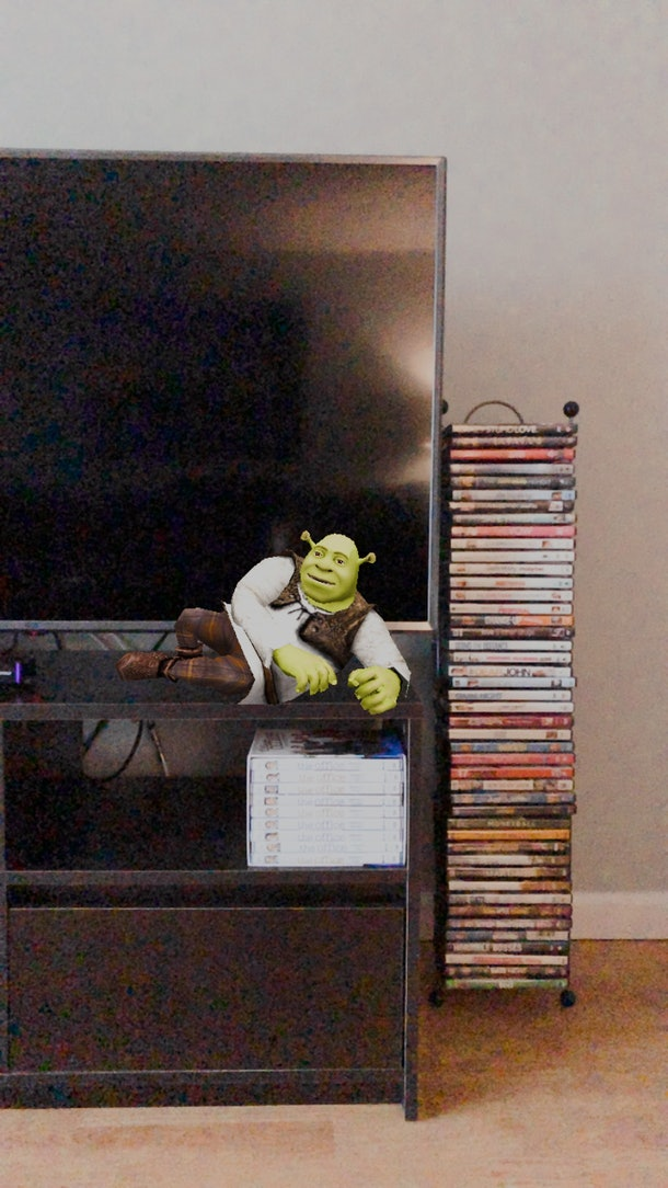 Shrek lounges on a television stand thanks to an Instagram story filter.
