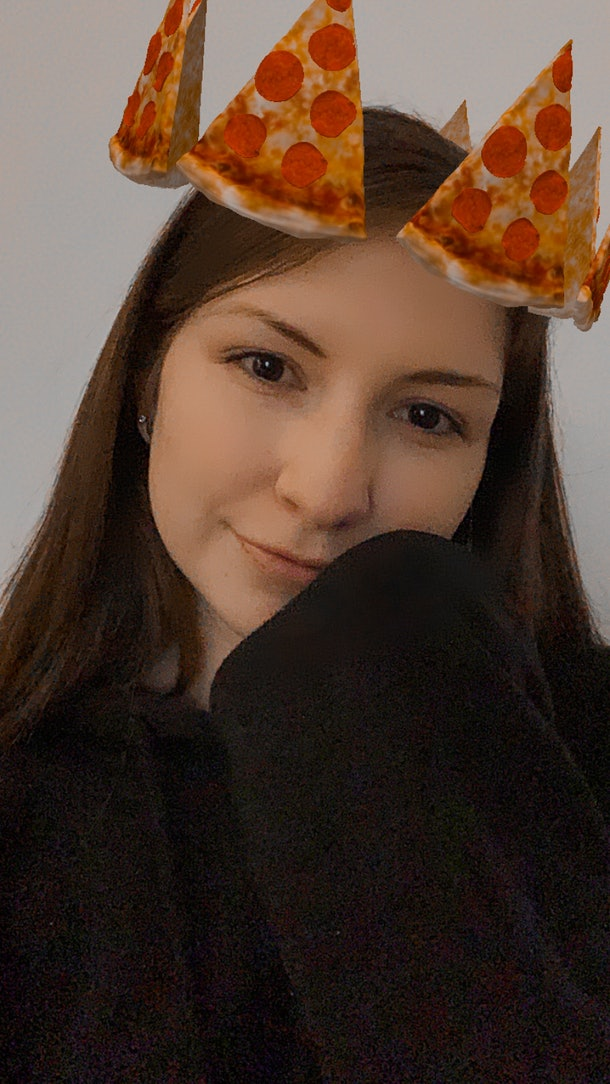 A young woman takes a selfie with an Instagram story filter that gives you a pizza crown.