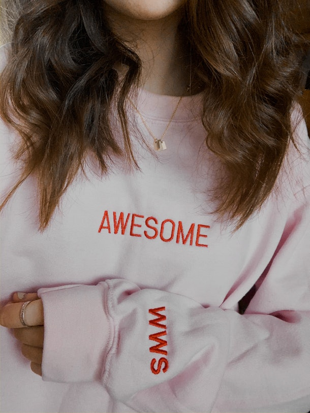"A young woman poses in a light pink sweatshirt that says, ""Awesome."""
