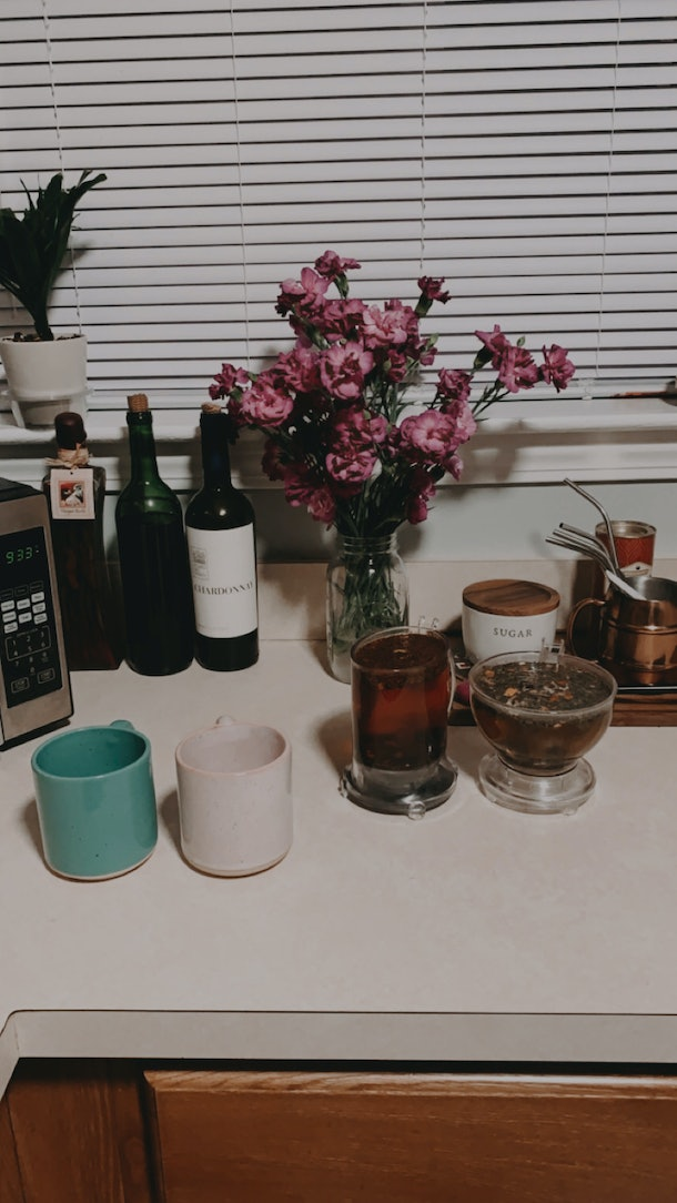 Colorful mugs sit on a kitchen counter while a couple brews fresh tea.