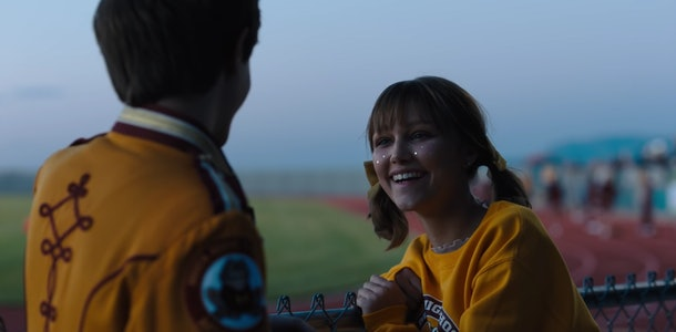 Stargirl and Leo laugh at a football game in the Disney+ movie.