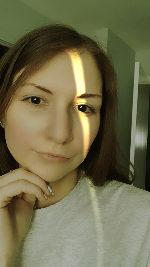 A young woman poses for a selfie with a light streak filter.