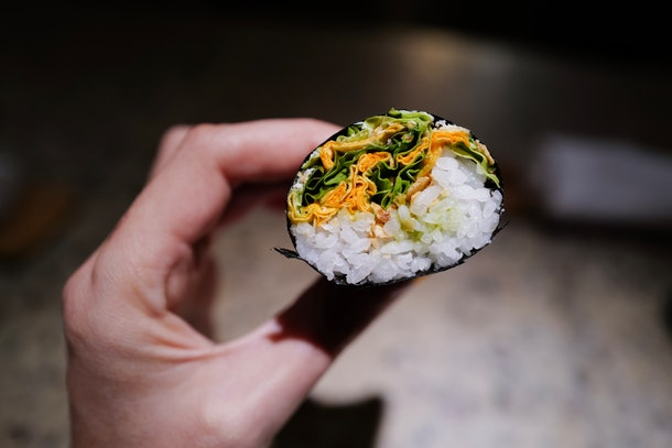 A woman's hand holds up a green salad hand roll at a restaurant in Mexico City.