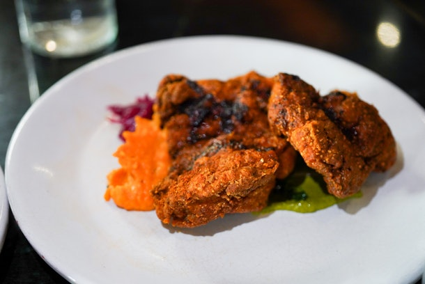 A white plate of masala fried chicken is at a restaurant in Mexico City.