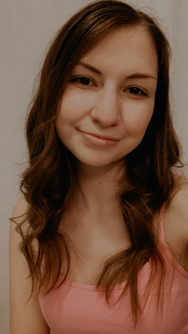 A young woman in a pink tank top poses for a selfie.