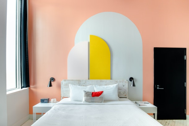 A custom mural room at Quirk Hotel in Richmond, Virginia has a modern and geometric design behind the bed's headboard.
