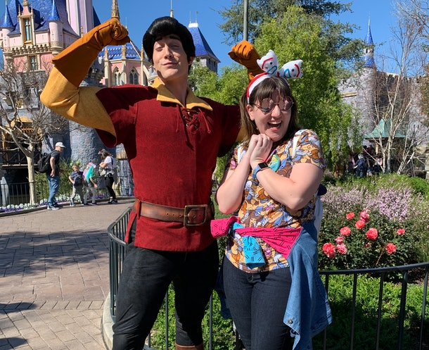 A woman with a jacket tied around her wait poses with Gaston from 'Beauty and the Beast' in front of the castle at Disneyland.