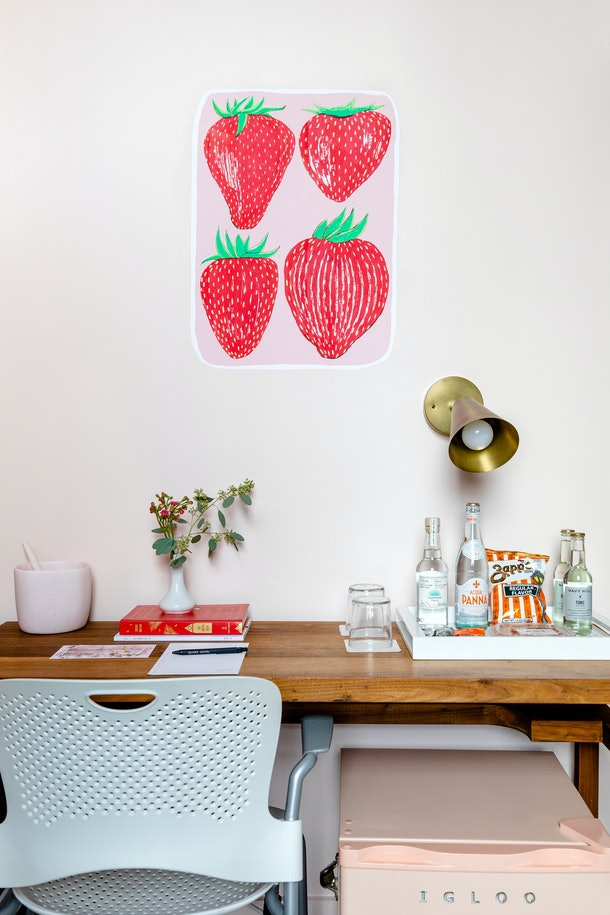 Strawberries are painted on the wall near a desk in a custom mural room at Quirk Hotel in Richmond, Virginia.