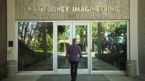 A man walks into the front doors of the Disney Imagineering building in California.