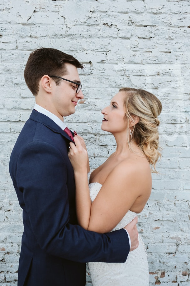 Rachel Varina and husband pose in front of white brick wall on wedding day