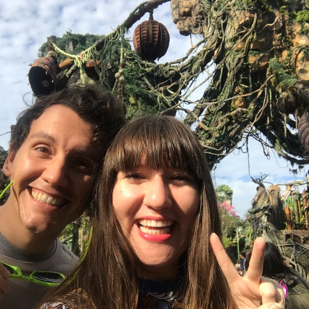 Two friends smile and pose while standing in front of a floating island designed by Imagineers at Disney World's Pandora — The World of 'Avatar.'