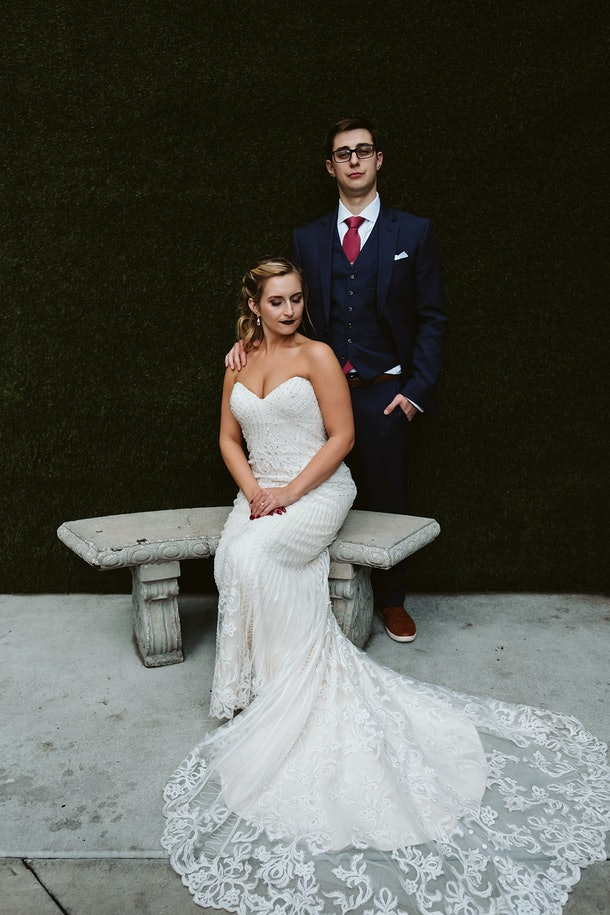 Rachel Varina in a Kitty Chen wedding gown poses on wedding day with husband in front of greenery wall