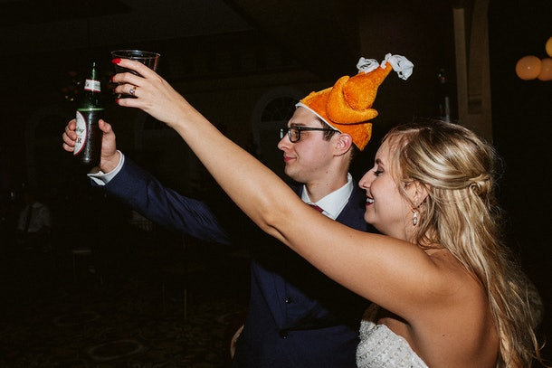 Rachel Varina and husband in turkey hat raise glasses for cheers at wedding reception