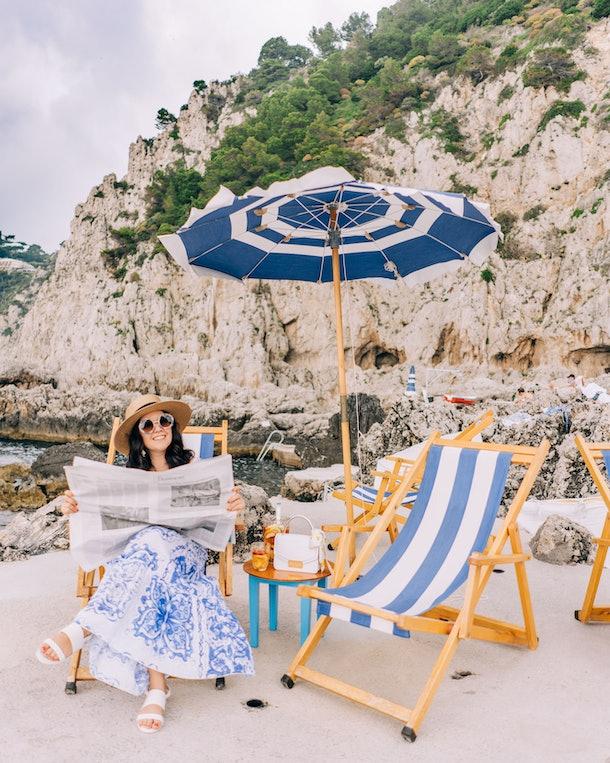 A woman sits on a striped beach chair while reading newspaper on a beach in Capri.