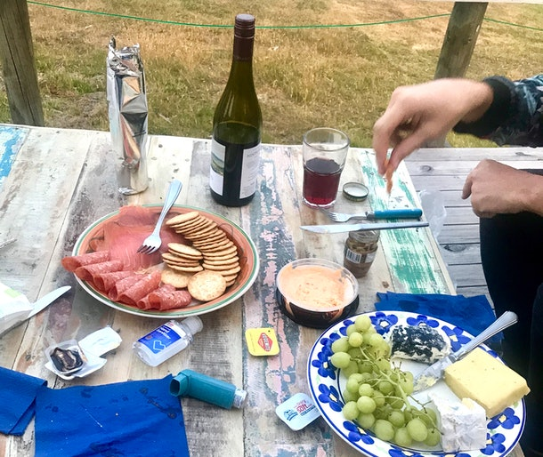 A picnic table has plates of meats, cheeses, and fruit on it.