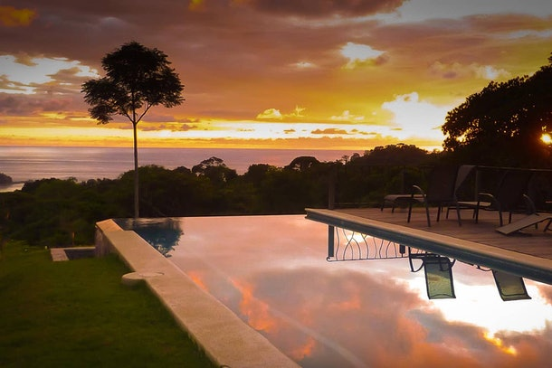 A pink and orange sunset reflects in the infinity pool of an Airbnb in Costa Rica.