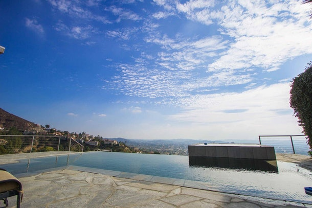 An infinity pool in California overlooks the Los Angeles hills at an Airbnb home.