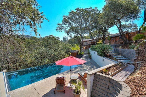 A pink umbrella and lounge chairs are next to an infinity pool in the mountains at a California Airbnb rental.