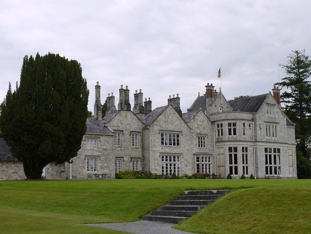 Lough Rynn Castle in Ireland features a stone exterior and massive green lawn.