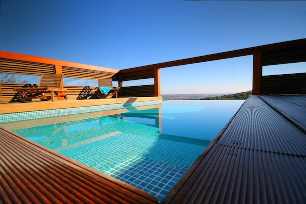 An infinity pool with a wooden deck is in the back of an Airbnb rental in Portugal.