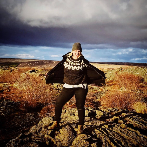 A woman wearing a beanie and winter sweater poses on a pile of rocks in a field on a sunny day.