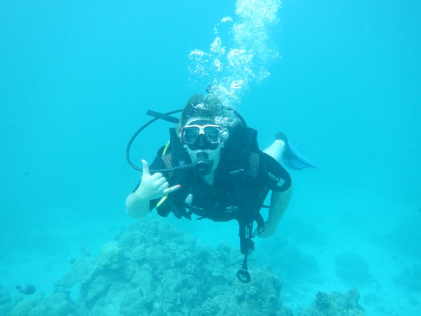 A woman poses for a picture while scuba diving.