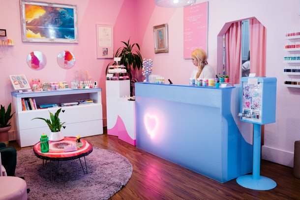 The interior of Cute Nail Studio in Austin, Texas features pink walls and colorful decor.