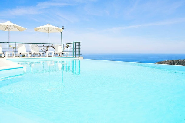 A blue infinity pool overlooks the ocean in this Airbnb rental in Greece.