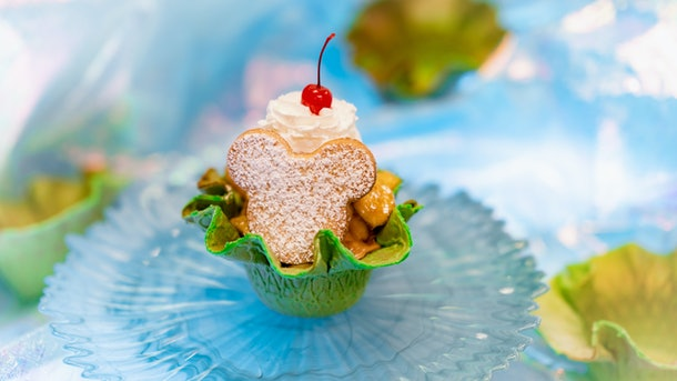 """A Mickey Mouse-shaped sugar cookie sit on top of an ice cream sundae in a green waffle bowl at Disneyland for the """"Magic Happens"""" parade."""