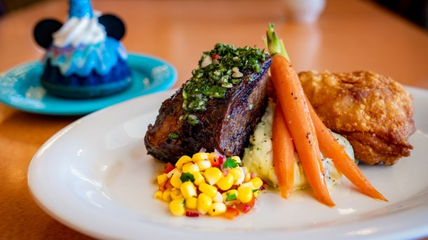"""Steak, carrots, mashed potatoes, and corn are on a plate with a colorful Mickey Mouse dessert in the background as part of Disneyland's new """"Magic Happens"""" parade."""