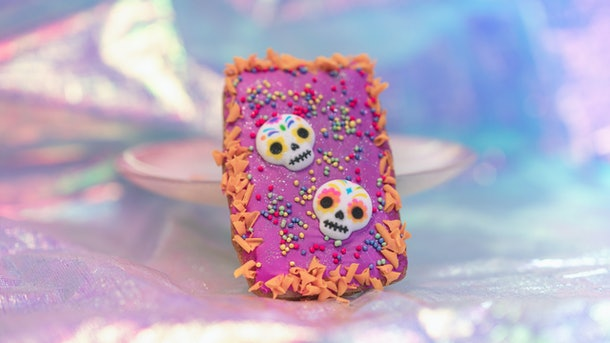 """A colorful Dia de los Muertos hand pie with sugar skulls leans against a plate and is served at Disneyland for the """"Magic Happens"""" parade."""