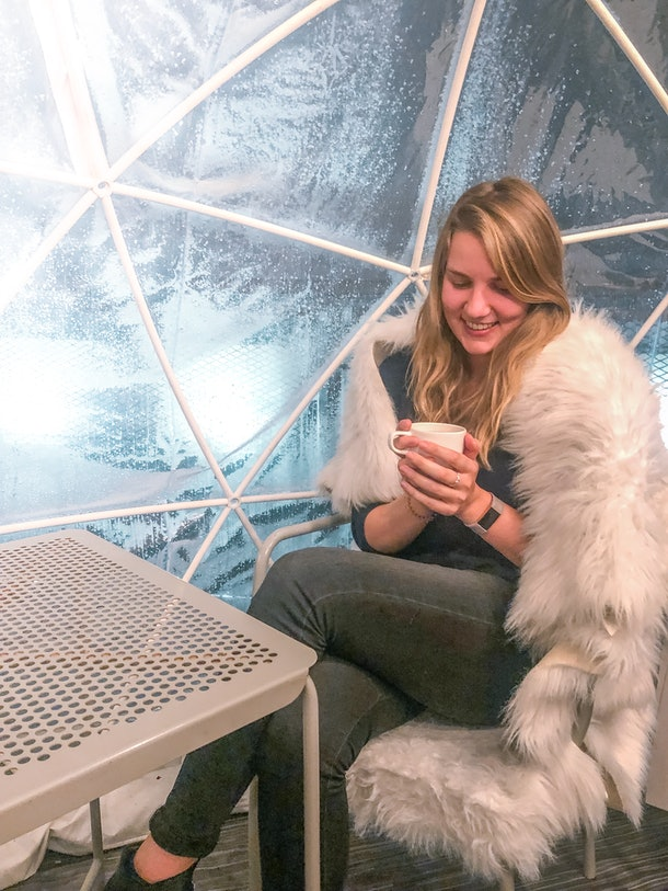 A woman smiles while holding a mug and sitting on a fuzzy chair at an igloo bar.