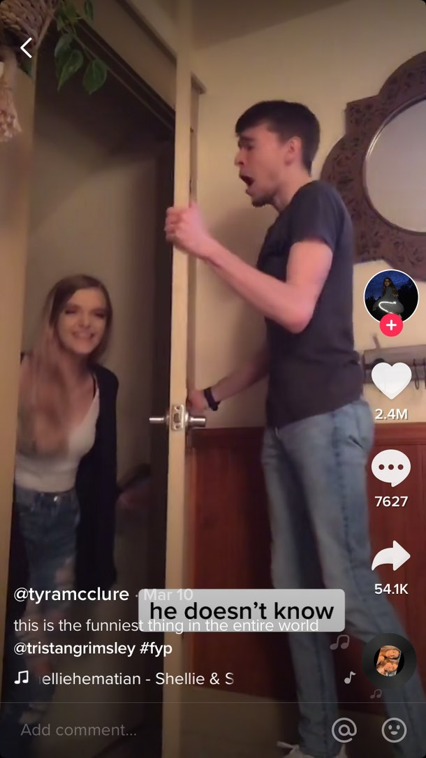 A woman backs out of the doorway as her boyfriend on the other side sings a song.
