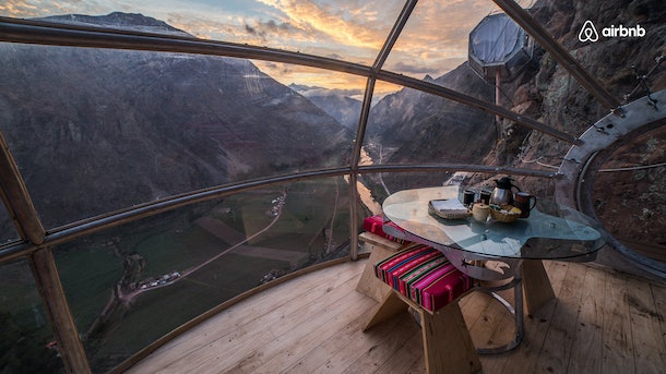 A skylodge in Peru is high above the ground in the mountains, with windows all around.