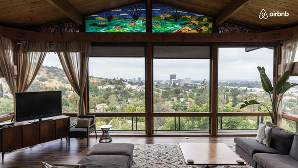 A vintage home in the Hollywood Hills has a large living room with windows all around.