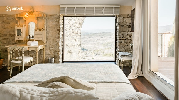 A home in France has rock walls and a white linen bed overlooking nature.