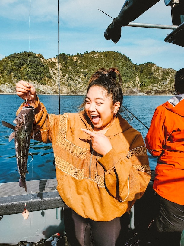 A woman in a yellow sweatshirt and leggings smiles and points to the fish she caught on a boat.