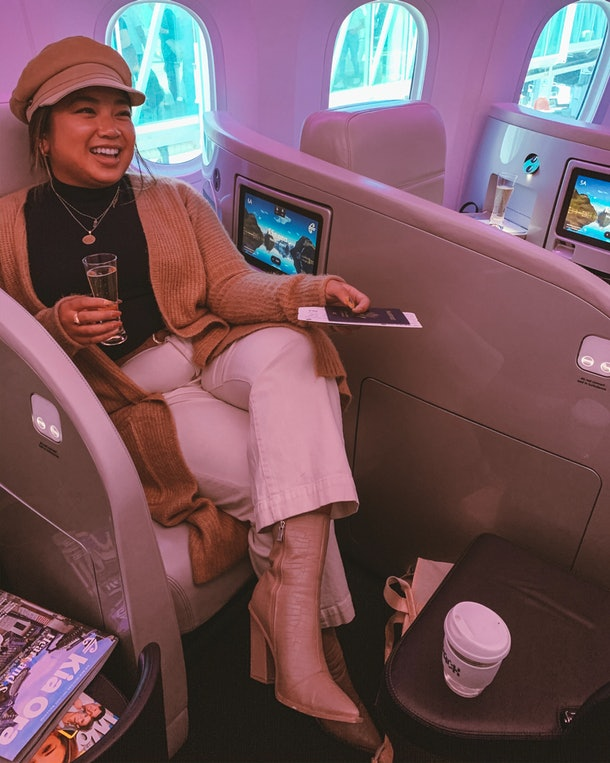 A woman wearing a long cardigan, white jeans, and booties smiles and sits in business class on an airplane.