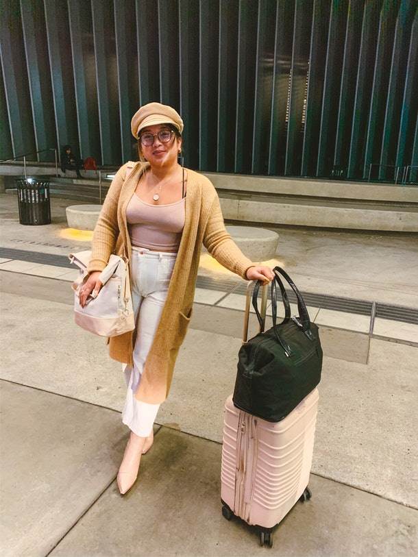 A woman wearing white pants, booties, a long cardigan and a hat poses with her rolling suitcase and carry-on bag outside an airport.