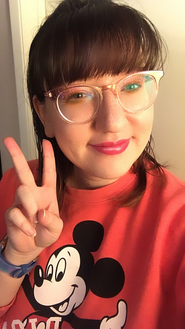 A woman gives a peace sign while wearing a Mickey Mouse sweater, and wearing glittery eye makeup from a filter.