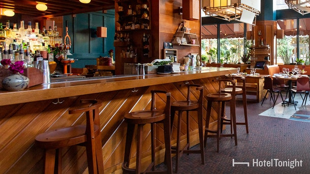 A restaurant bar in Los Angeles, California features cozy barstools and a moody atmosphere.