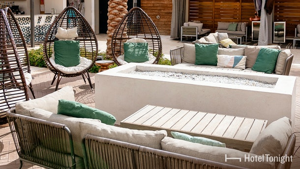 An outdoor patio of a hotel features white and teal furniture, and a lighthearted atmosphere.