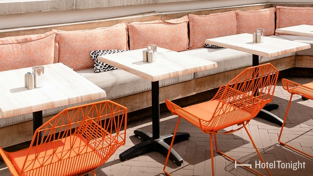 A hotel patio is glowing in the sun, and perfectly designed with orange and pink pieces.