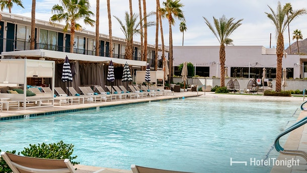 A hotel pool in Scottsdale, Arizona is surrounded by palm trees and adorable lounge chairs.