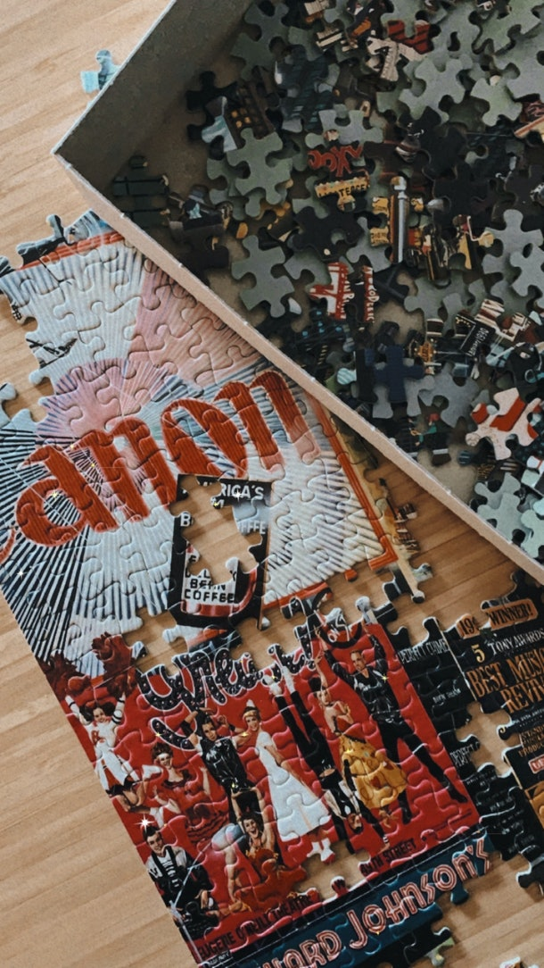 A colorful puzzle of Times Square is laid out on a kitchen table.