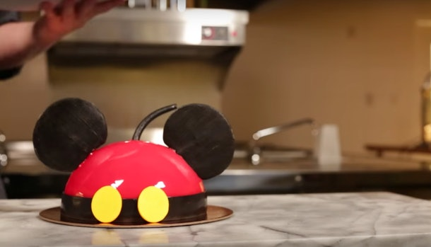 A Mickey Mouse-shaped dome cake sits on the counter in a kitchen.